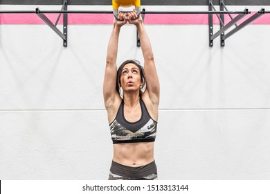 beautiful and young woman doing exercises with the kettel belt