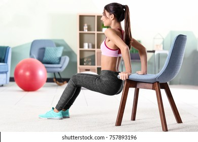 Beautiful young woman doing exercises with chair at home
