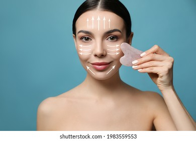 Beautiful young woman doing facial massage with gua sha tool on blue background, closeup