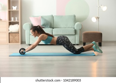 Beautiful young woman doing fitness exercise with roller wheel at home