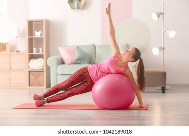 Beautiful young woman doing fitness exercise with ball at home