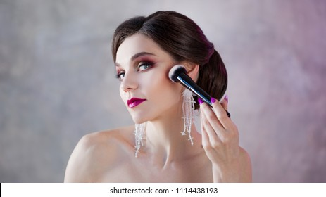 A beautiful young woman is doing herself a makeover. Girl with brush in hand to apply powder on face