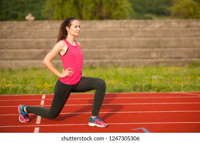 Beautiful young woman doing longe step on athletic track