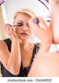 Beautiful young woman is doing makeup in front of the mirror.