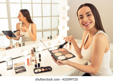 Beautiful young woman is doing makeup using a blusher, looking at camera and smiling, sitting in front of the mirror