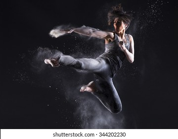 Beautiful young woman doing martial arts with flour powder over dark background.