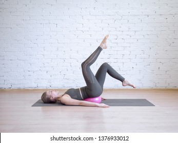 Beautiful young woman doing pilates workout with small pink fitness ball, leg arch exercise. Indoor, loft background, toned blue. Wellness, recovery, rehabilitation, prevention spine desease, smart