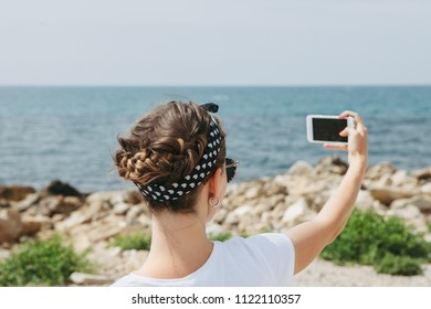 Beautiful young woman  doing selfie in the summer day near the sea