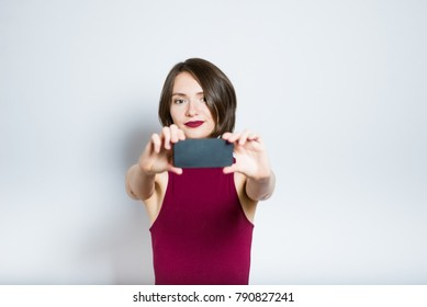 beautiful young woman doing selfie photo on phone, in red evening dress, isolated on background