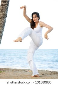 A beautiful young woman doing a silly and funny yoga pose on a beach.