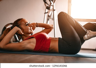 Beautiful young woman doing sit-up in her living room.
