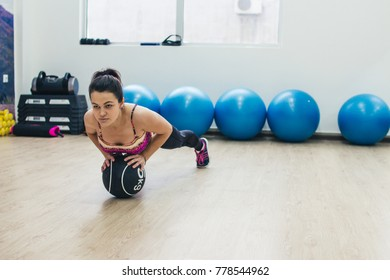Beautiful young woman doing some gymnastics at the gym with ball.