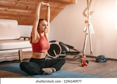 Beautiful young woman doing stretching exercises at her home.