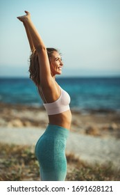 A beautiful young woman is doing stretching exercise at the sea beach in summer sunny day.