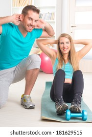 Beautiful young woman doing stretching exercises with personal trainer at home