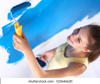 Beautiful young woman doing wall painting , standing