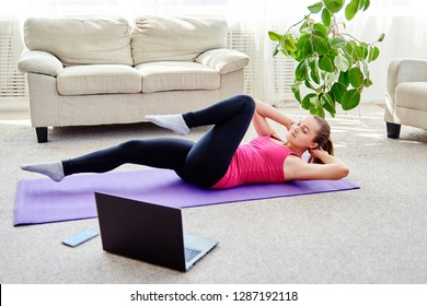 Beautiful young woman doing working out exercise on floor at home, online training on laptop computer, copy space. Yoga, pilates exercising. Sport, healthy lifestyle concept
