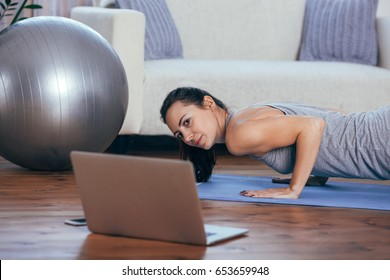 Beautiful young woman doing workout at home
