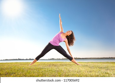 Beautiful young woman doing yoga exercise on green grass next to the  lake. Yoga concept.