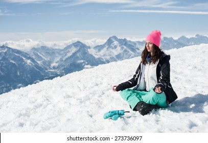 Beautiful young woman doing yoga in the snow mountains. Winter Scenic in the French Alps, Les 2 Alpes
