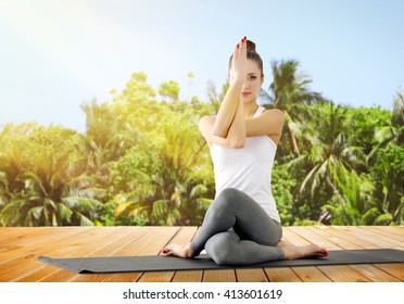 Beautiful young woman doing yoga on nature