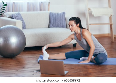 Beautiful young woman doing yoga at home.