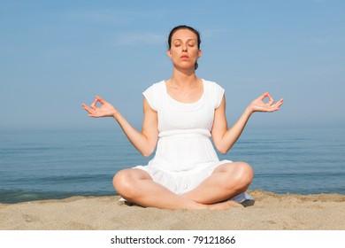 Beautiful Young Woman Doing Yoga Exercises at Seaside