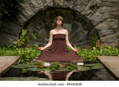 Beautiful young woman doing yoga exercise outdoors in an 18th century water garden.