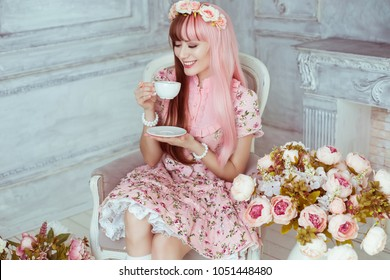 Beautiful young woman doll in a pink dress, in a bright room and flowers sitting in a chair with a cup, tea party, lolita. Japanese street fashion. Portrait.