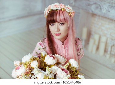 Beautiful young woman doll in a pink dress, in a bright room and flowers, lolita. Japanese street fashion. Portrait.