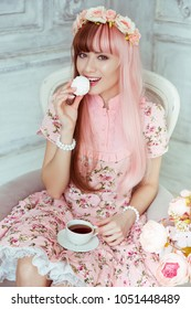 Beautiful young woman doll in a pink dress, in a bright room and flowers sitting in an armchair with a cup and a ze, tea party, lolita. Japanese street fashion.