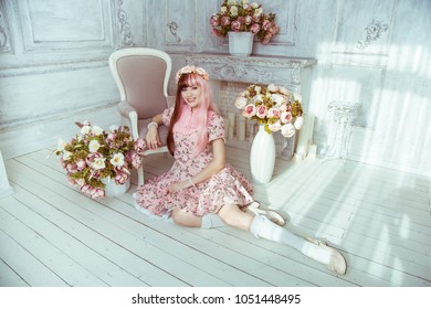 Beautiful young woman doll in a pink dress, in a bright room and flowers sitting on the floor leaning against an armchair, lolita. Japanese street fashion.