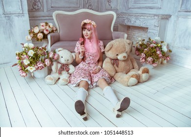 Beautiful young woman doll in a pink dress in a room with flowers, sits on the floor with toys and plush bear, lolita. The dere is in his hand lollipop.