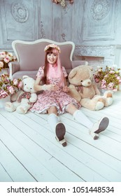 Beautiful young woman doll in a pink dress in a room with flowers, sits on the floor with other toys and plush bear, lolita. Japanese street fashion.