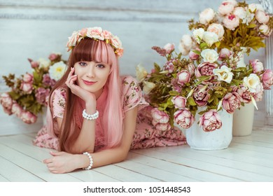 Beautiful young woman doll in a pink dress lies on the floor in a bright room and flowers, lolita. Japanese street fashion. Portrait.