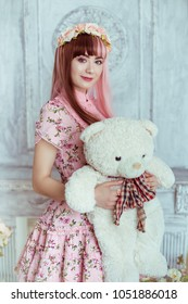 Beautiful young woman doll in pink dress in the room, with toys and plush bear, lolita. Japanese street fashion.
