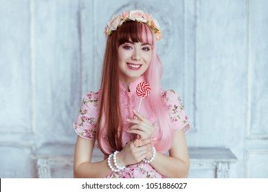 Beautiful young woman doll in a pink dress, with a lollipop, lolita. Japanese street fashion. Portrait.