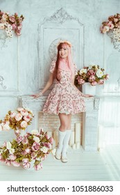 Beautiful young woman doll in a pink dress, in a bright room and flowers stands by the fireplace, lolita. Japanese street fashion.