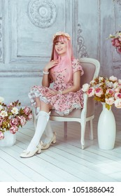 Beautiful young woman doll in a pink dress in a room with flowers, sitting on a chair by the fireplace, lolita. Japanese street fashion.