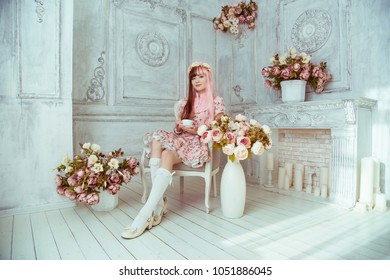 Beautiful young woman doll in a pink dress, in a bright room and flowers sitting in a chair with a cup, tea party, lolita. Japanese street fashion.