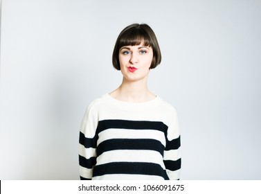 beautiful young woman doubts skeptic, short haircut, studio photo on background