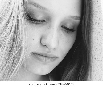 Beautiful young woman with downcast eyes and a serious serene expression, close up greyscale face portrait