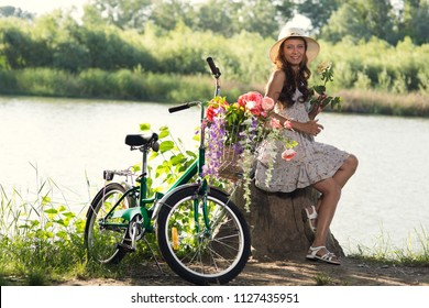 Beautiful Young Woman in a Dress and Hat on a Bicycle on the Nature in the Park Among the Grass and Trees