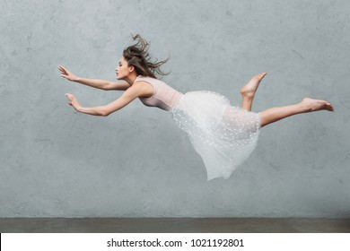 beautiful young woman in dress levitating and looking away on grey