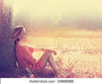 Beautiful young woman in a dress on the nature dreams