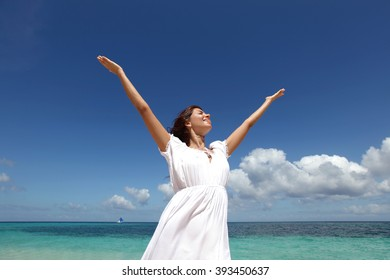 Beautiful young woman in dress on beach with hands raised