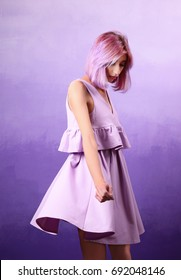 Beautiful young woman in dress on lilac background