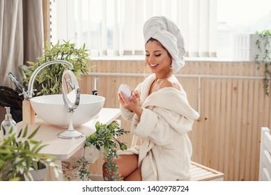 Eine schöne junge Frau, die in einem Bademantel gekleidet ist, macht sich im Badezimmer einen Schmink. Konzept der Schönheit und Make-up.