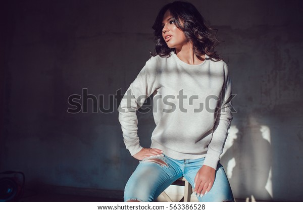 Beautiful young woman dressed in blank sweatshirt sitting on a gray background. Mock-up.