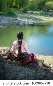 Beautiful young woman dressed in Boho style, sits on a rock by the river bank and looks at the distance, enjoying the view of nature.